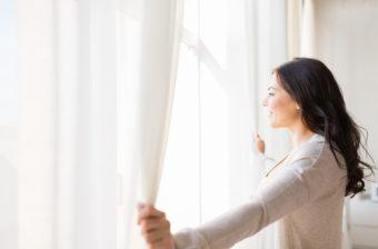Bien-être : Femme qui ouvre un rideau devant une fenêtre